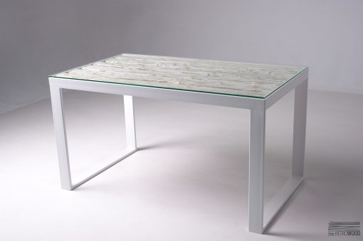 Stół Bergen wykonany z ciężkiej i solidnej stalowej ramy i blatu ze starych desek. Całość zwieńczona jest taflą grubego hartowanego szkła.