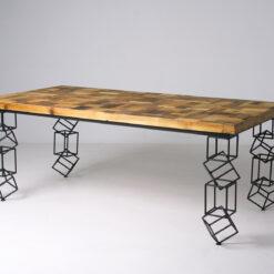 Stół Cubino od razu przyciąga wzrok pięknym wykonaniem metalowych nóg oraz drewnianym blatem w różnych odcieniach brązu, wykonanym ze starego drewna.