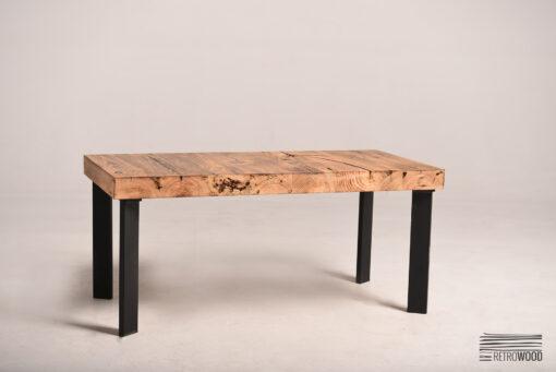 Ten prostokątny stolik posiada szeroki blat oraz podstawę ze stali.